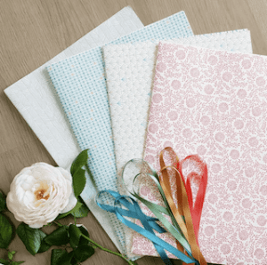 Sélection de papiers cadeaux et de rubans de 4 couleurs et motifs différents de la marque Les Belles Musettes afin d'emballer ses cadeaux de manière éco-responsable